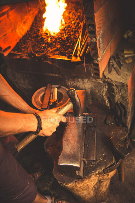 Anonymous man using hummer to forge blade from piece of metal in professional workshop — Stock Photo