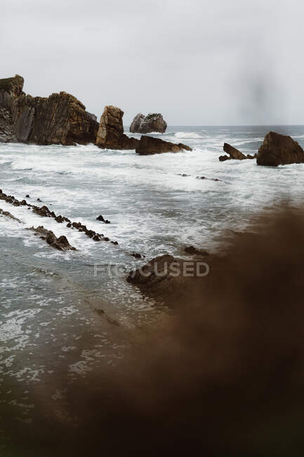 Rocks in wavy seaunder gray cloudy sky in Cantabria, Spain — Stock Photo
