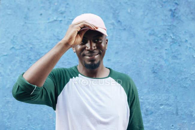 Африканський чоловік з чорною бородою, одягнений у біле з зеленою сорочкою з рожевим ковпаком на розмитому синьому фоні стіни. — стокове фото