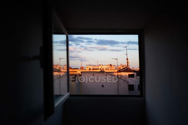 На вікні відчинилися помешкання з антенами під блакитним хмарним небом. — стокове фото