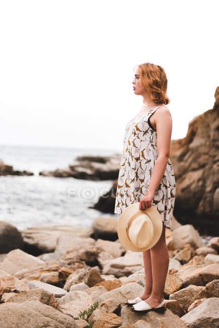 Vista posteriore della donna tatuata in cappello in piedi su pietre con le mani divaricate e guardando l'oceano — Foto stock