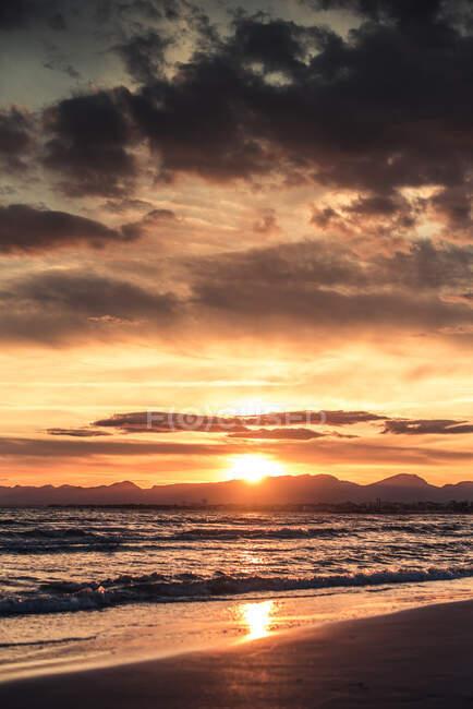 Coucher de soleil incroyable sur le rivage paisible de l'océan — Photo de stock