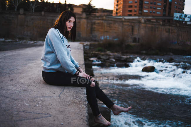 Side view of casual brunette in hoodie sitting barefoot on concrete waterfront with waves below and looking away. — Stock Photo