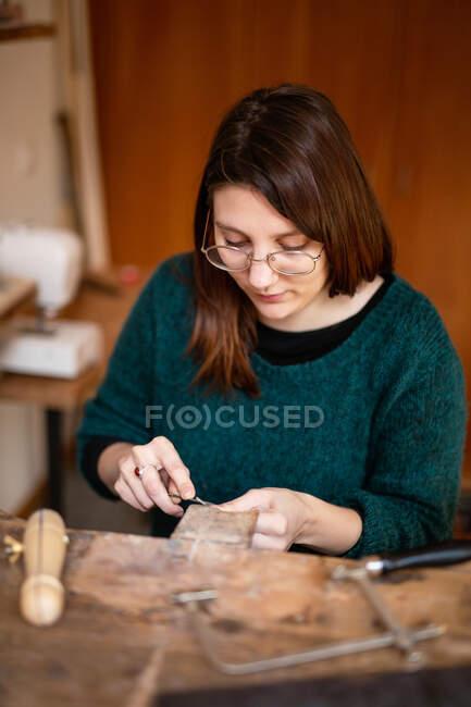 Mulher concentrada em blusa verde e óculos escultura decoração com instrumento na mesa de trabalho na oficina — Fotografia de Stock