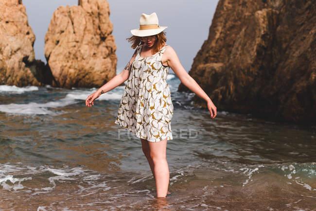 Mujer bonita en sombrero de pie y relajante en el océano en grandes rocas - foto de stock