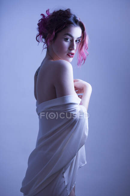 Vista lateral da mulher atraente tirando o pano branco e olhando para a câmera no estúdio. — Fotografia de Stock