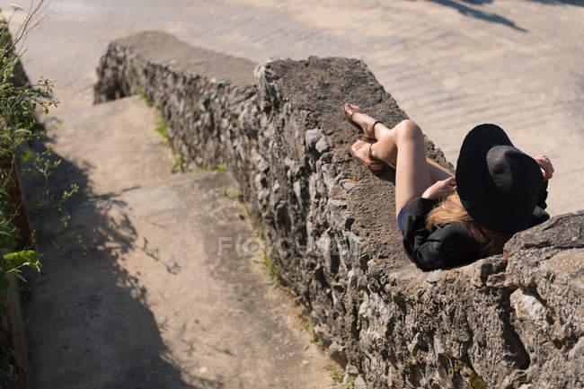 Mujer en traje elegante y sombrero acostado en la antigua frontera de piedra en el día soleado y descansando - foto de stock