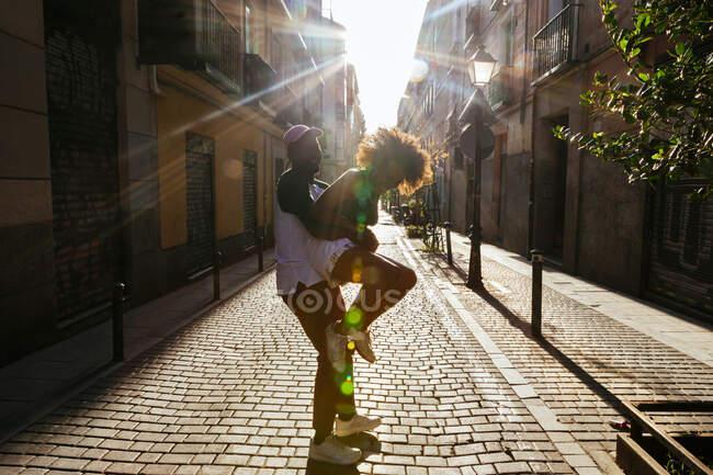 Afroamericano uomo holding fidanzata a strada — Foto stock