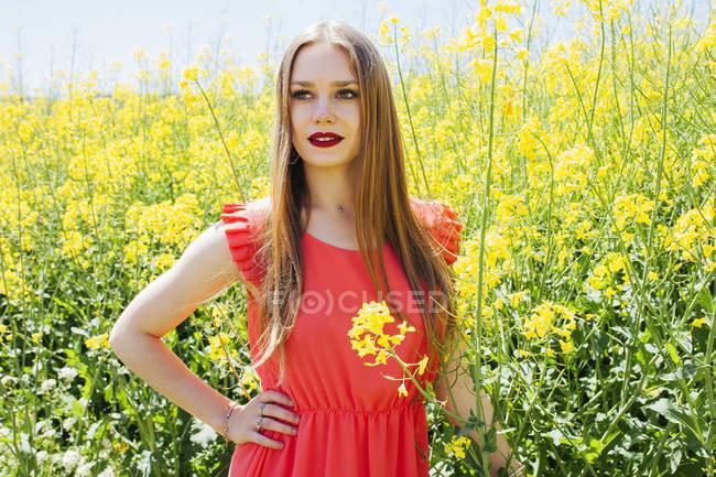 Jeune femme romantique en robe rouge debout en fleurs d'été — Photo de stock