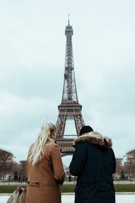 Пара, стоящая на Эйфелевой башне в пасмурный день в Париже, Франция. — стоковое фото