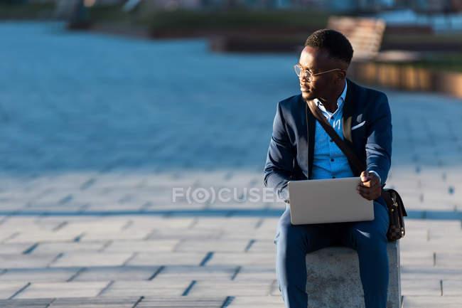 Funky бізнесмен сидить з ноутбука на вулиці і дивитися вбік — стокове фото