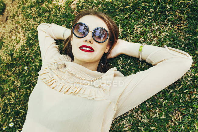 Young stylish woman in fashionable sunglasses lying on green grass and looking at camera — Stock Photo