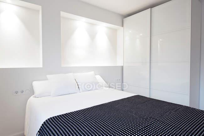 Удобная кровать, стоящая рядом со шкафом в красивой светлой комнате. — стоковое фото