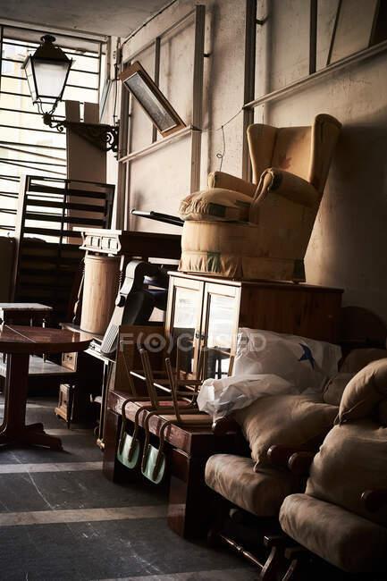 Muebles viejos colocados en un montón en el suelo de la habitación sin papel pintado - foto de stock