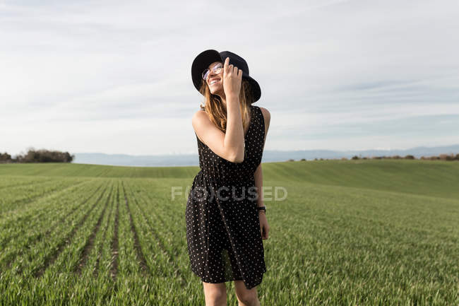 Happy woman in hat and polka-dot dress posing in field — Stock Photo