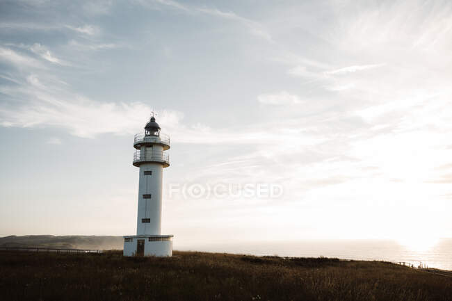 Retro beacon illuminated by sun on blue sky background in Cantabria, Spain — Stock Photo