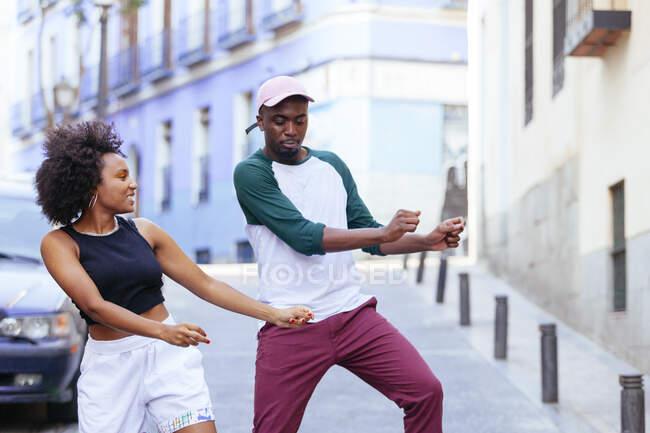 Feliz hombre y mujer afroamericanos con ropa elegante bailando juntos en la calle — Stock Photo