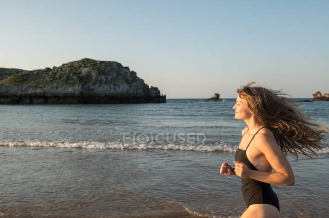 Jovem mulher em traje de banho correndo perto do mar — Fotografia de Stock