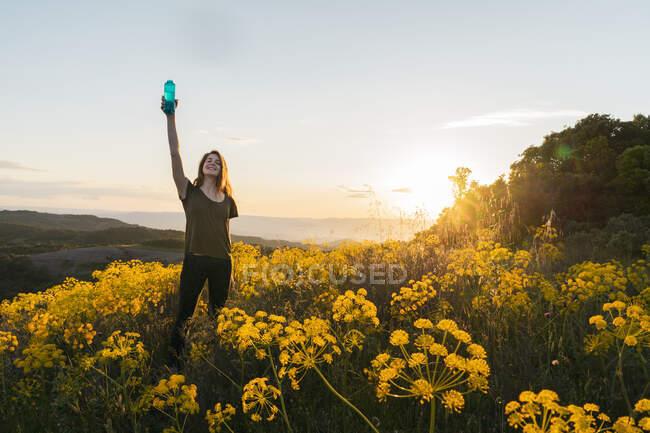 Mujer bebiendo agua de pie entre flores silvestres - foto de stock