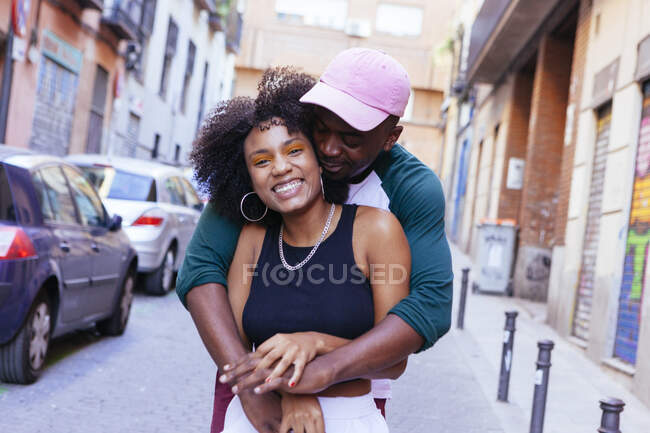 Female in dark blue t-shirt and orange eye shadows?embraced by male in azure shirt and pink cap?hugging and looking at camera on blurred street background — Stock Photo