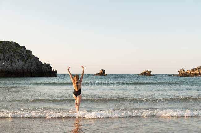 Silhouette of woman standing in sea with arms up — Stock Photo