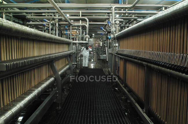 Oficina de fábrica de filtro de cerveja com tubos de cobre abaixo do teto e trabalhador em uniforme branco — Fotografia de Stock