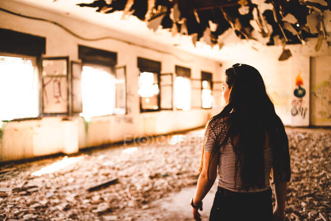 Charming young woman standing under decorated roof of light pavilion and looking down — Stock Photo