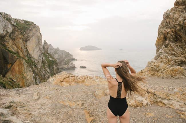 Frau im schwarzen Badeanzug auf felsigen Ufer stehen und betrachten — Stockfoto