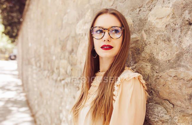 Élégant femme réfléchie dans des lunettes appuyé sur le mur de pierre à l'extérieur — Photo de stock