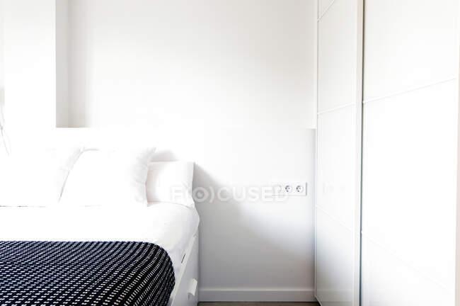 Cama confortável em pé perto de guarda-roupa em sala de luz agradável. — Fotografia de Stock