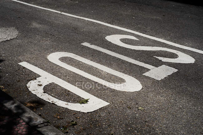 From above view of gray asphalt road with Stop inscription painted with white color — Stock Photo