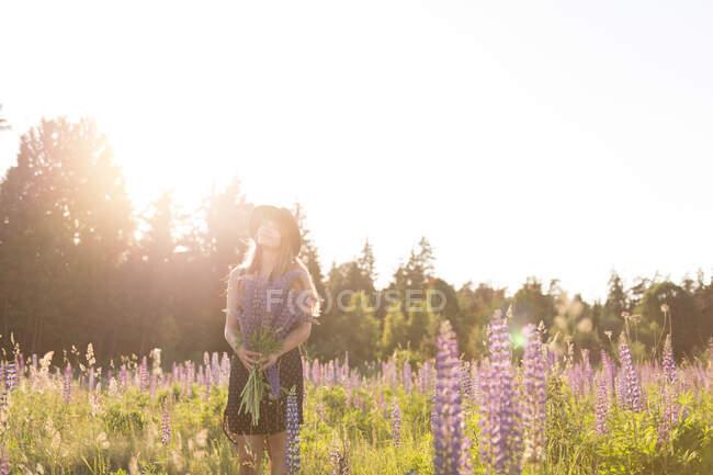 Femme anonyme en chapeau et robe debout avec un bouquet de fleurs dans ? blooming champ dans rétro-éclairé lumineux — Photo de stock