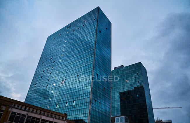 Desde abajo vista de majestuosos edificios altos contemporáneos con muchas ventanas de cristal bajo el cielo azul nublado de Bilbao - foto de stock