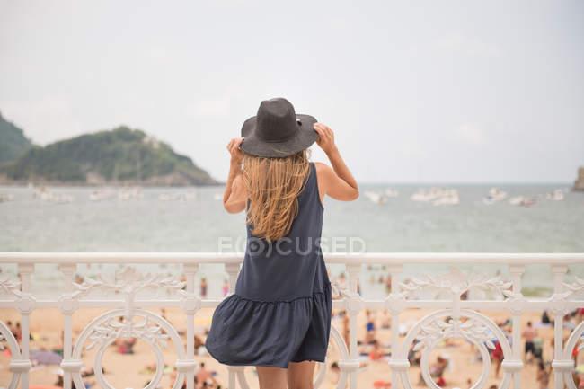 Rückansicht des jungen Frau hält Hut und genießen Aussicht auf überfüllten Strand und ruhige Meer stehen in der Nähe von Zaun — Stockfoto