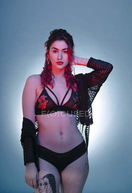 Sensual young attractive woman in black lingerie holding head in studio. — Stock Photo