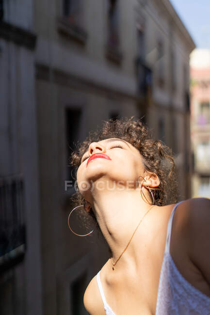 Sensual curly woman in white lace bra keeping eyes closed and enjoying bright sunlight on balcony — Stock Photo