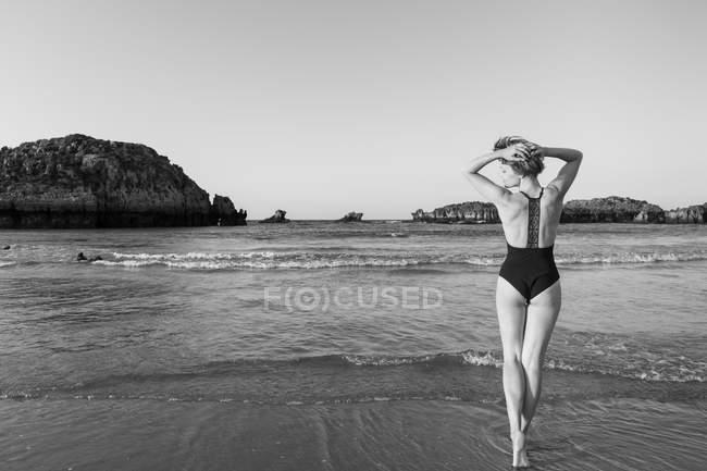 Vista posteriore donna in costume da bagno nero in piedi vicino al mare — Foto stock