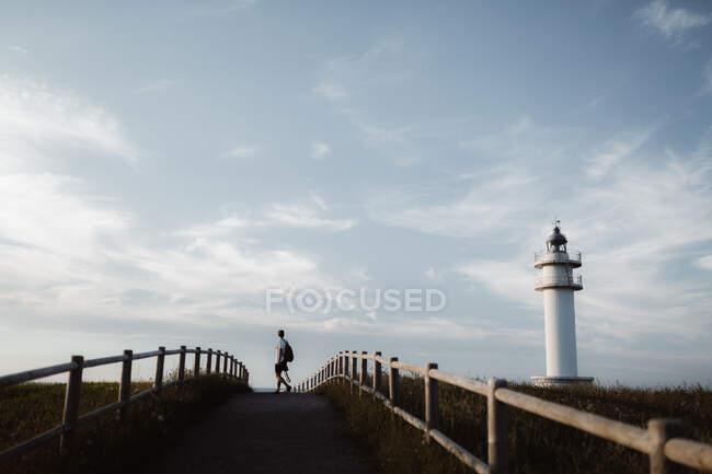 Man on footpath near lighthouse — Stock Photo