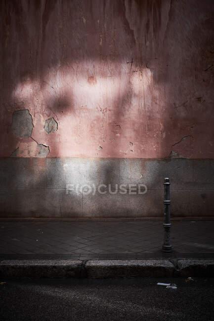 Mur en pierre rouge avec fissures et ombre dans la rue sombre — Photo de stock