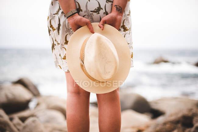 Vista posteriore della donna delle colture in possesso di cappello e in piedi sulla costa rocciosa al mare — Foto stock