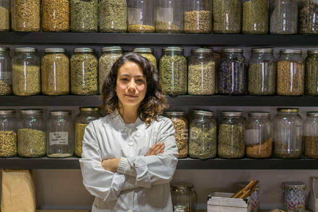 Pretty shop assistant woman standing with arms crossed at shelves with spices. — стокове фото