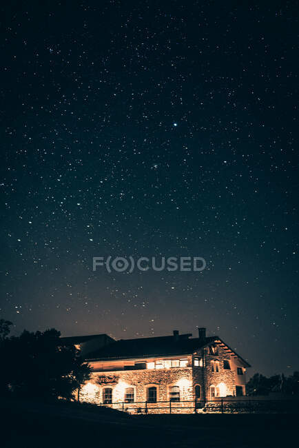 Glowing houses in countryside in starry night — Stock Photo