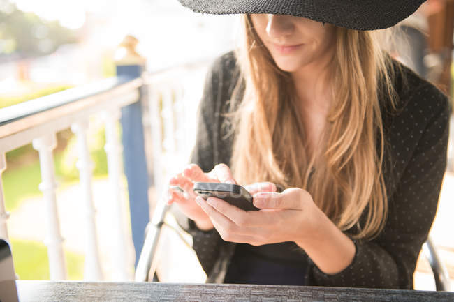Woman in elegant outfit sitting at table with smartphone — Stock Photo