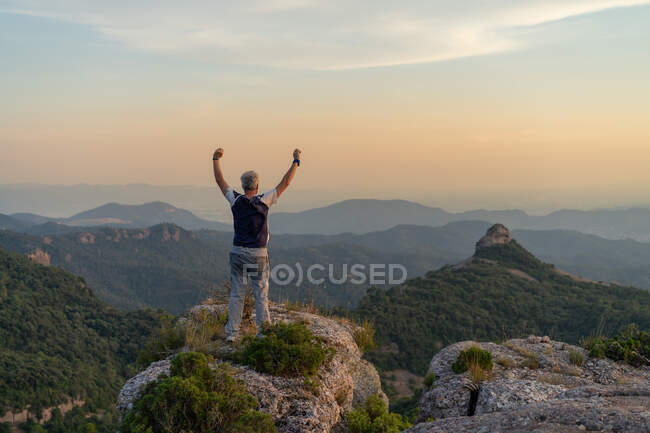 Back view of elderly man keeping hands up and admiring amazing view while standing on top of mountain in Tossaff - foto de stock