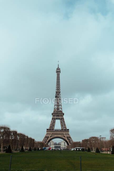Вид на большой зеленый лаун и Эйфелеву башню на фоне облачного неба в Париже, Франция. — стоковое фото