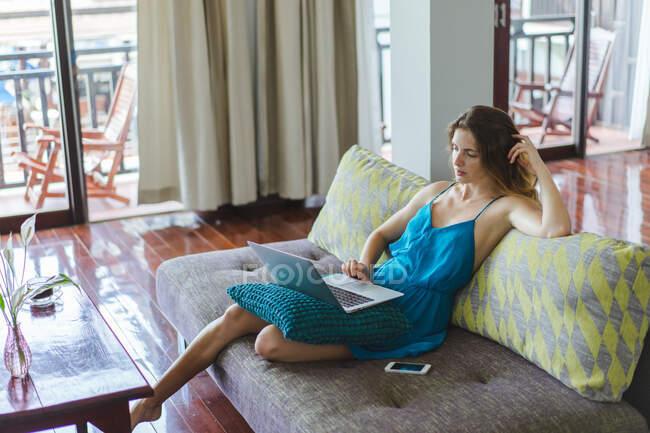 Mujer descansando y usando portátil - foto de stock