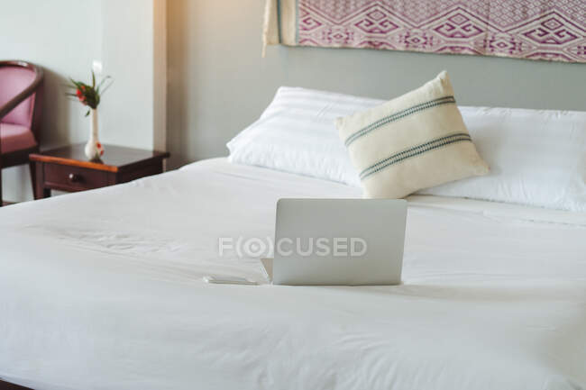 Gray modern laptop placed on the bed in the apartment — Stock Photo