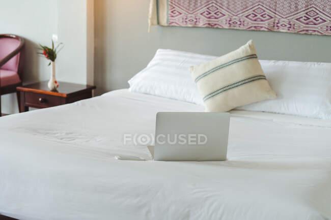 Сірий сучасний ноутбук, поміщений на ліжку в квартирі. — стокове фото