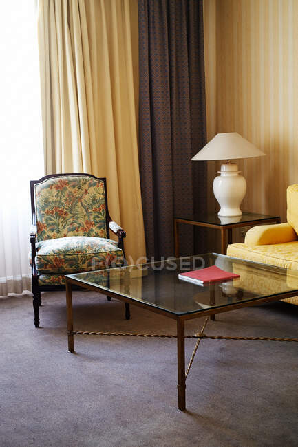 Glass table with book on top and comfortable armchairs with patterned cover placed in room with striped wallpaper and curtains — Stock Photo