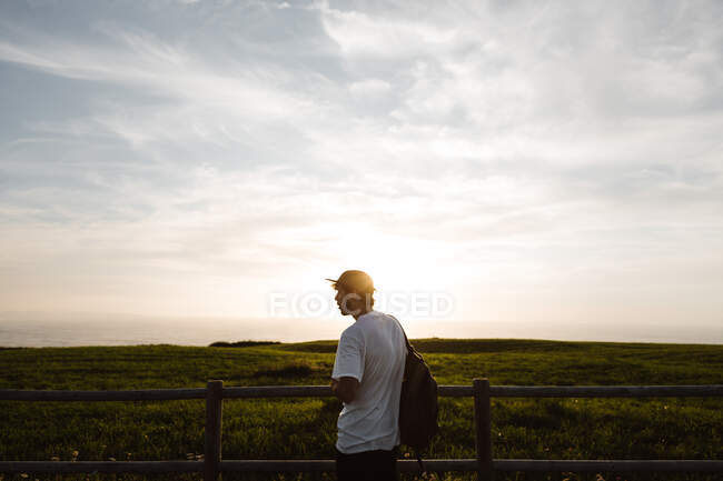 Man leaning in a fence in forest — Stock Photo